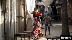 ARCHIVES - Un femme marche à travers un marché déserté après à la suite des manifestations contre la candidature de Pierre Nkurunziza pour un troisième mandat à Bujumbura, le 29 avril 2015.