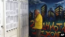 Seorang warga Yunani tengah memeriksa daftar pilihan di salah satu TPS di Athena (17/6). Yunani menyelenggarakan pemilu ulang yang dapat menentukan arah kebijakan negara yang terlilit hutang di Zona Euro itu.