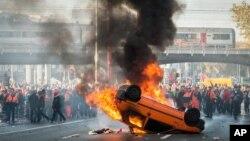 Người biểu tình đứng đằng sau một chiếc xe đang cháy trong một cuộc biểu tình của công đoàn quốc gia ở Brussels, 6/11/2014.
