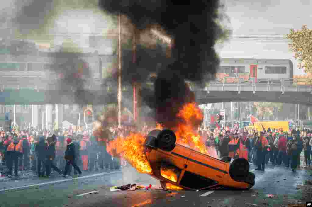 Protesters stand behind a burning car during a national trade union demonstration in Brussels, Belgium, Nov. 6, 2014.