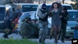 Anggota milisia pro-Rusia mengevakuasi warga saat pasukan Rusia menyerang pangkalan udara Belbek, di luar Sevastopol, Krimea, Sabtu (22/3). (AP/Ivan Sekretarev)