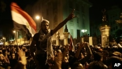 Egyptian protesters chant anti-Muslim Brotherhood and Egyptian President Mohammed Morsi slogans outside the presidential palace after they broke a barbed wire barricade keeping them from getting closer to the presidential palace, in Cairo, Dec. 7, 2012.