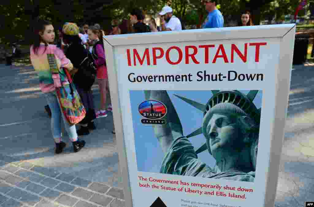 Tourists walk by a sign announcing that the Statue of Liberty is closed due to a U.S. government shutdown in New York. Government institutions and national parks were closed and thousands of employees were furloughed after Congress was unable to agree on a federal budget and shut down the goverment for the first time in 17 years.