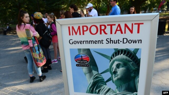 Tourists walk by a sign announcing that the Statue of Liberty is closed due to a US government shutdown in New York, October 1, 2013.