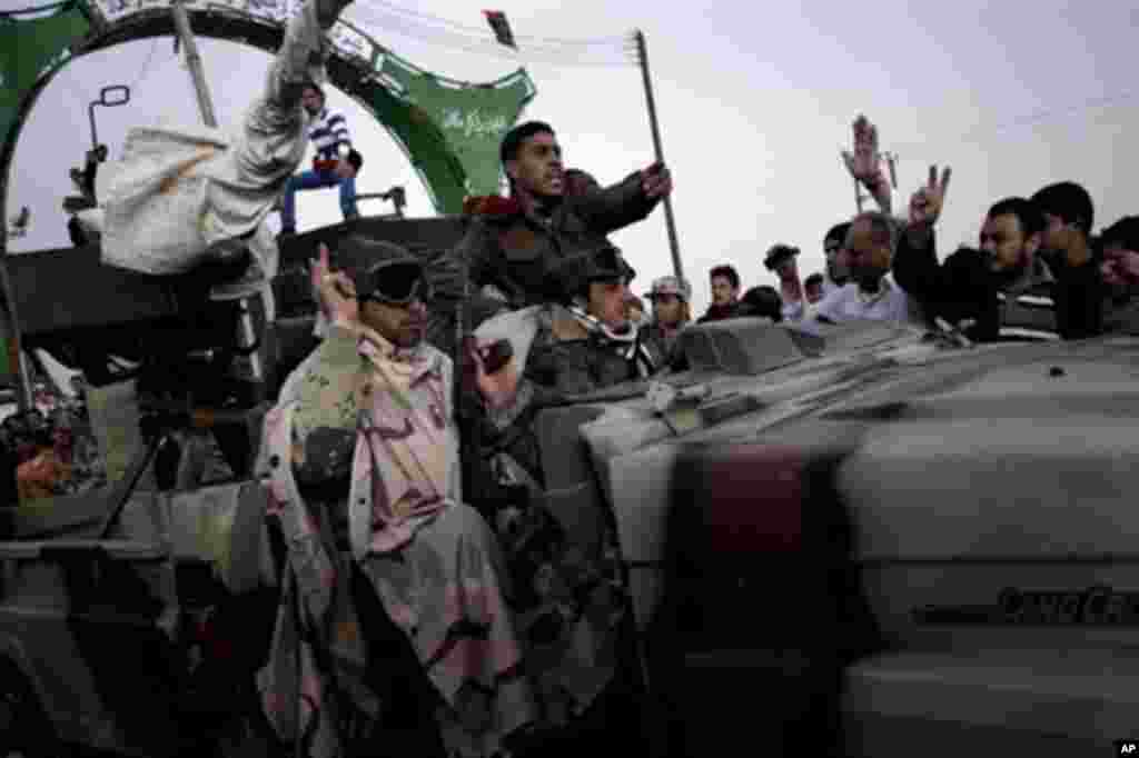 Libyan rebel fighters celebrate as they pass through Ajdabiya's west gate, 160 kms west of Benghazi, on their way to Ras Lanuf where heavy fighting is taking place with loyalist forces, March 04, 2011. (AFP Image)