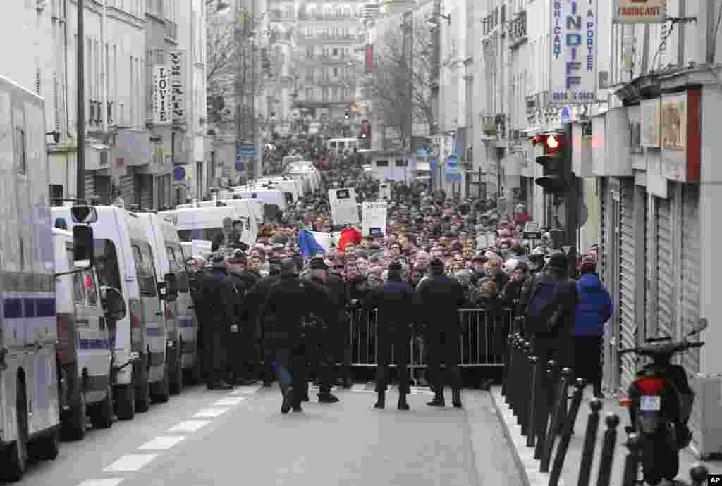 Police block a street to hold back the public demonstration near Place de la Republique in Paris, Jan. 11, 2015.