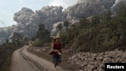 Seorang warga desa berlari menghindari letusan Gunung Sinabung di desa Sigarang-Garang, distrik Karo, Sumatera Utara (1/2).