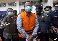 Menteri Kelautan dan Perikanan Edhy Prabowo (tengah) dikawal petugas keamanan setelah konferensi pers di kantor Komisi Pemberantasan Korupsi (KPK), Jakarta, Kamis, 26 November 2020. (AP)