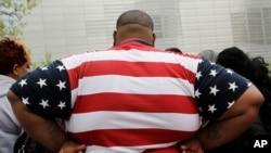 一位身體過重的男士身穿美國國旗圖案的T恤衫參觀紐約世貿中心。