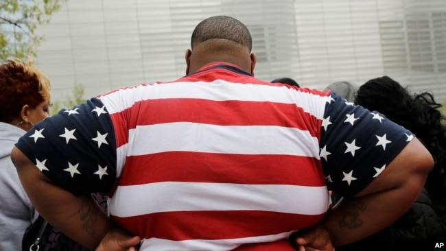 資料照:一位身體過重的男士身穿美國國旗圖案的T恤衫參觀紐約世貿中心。