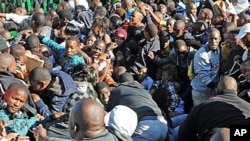 Thousands of young students and their parents push their way into the gates of the University of Johannesburg, South Africa, Jan. 10, 2012.