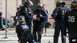 Un homme blessé dans des affrontements entre supporters est assisté par des policiers dans le centre de Marseille, France, 11 juin 2016. (AP Photo / Darko Bandic)