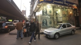 People walk past a foreign currency exchange center in Cairo (file photo).