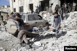 FILE - Residents carry an injured woman on a stretcher in a site hit by airstrikes in the rebel-controlled area of Maarat al-Numan town in Idlib province, Syria, Jan. 9, 2016.