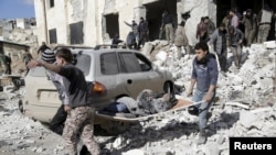 Suriyanın İdlib vilayətinin Maarat Əl-Numan şəhərinin sakinləri hərbi hava hücumlarından sonra yaralananlara yardım edir