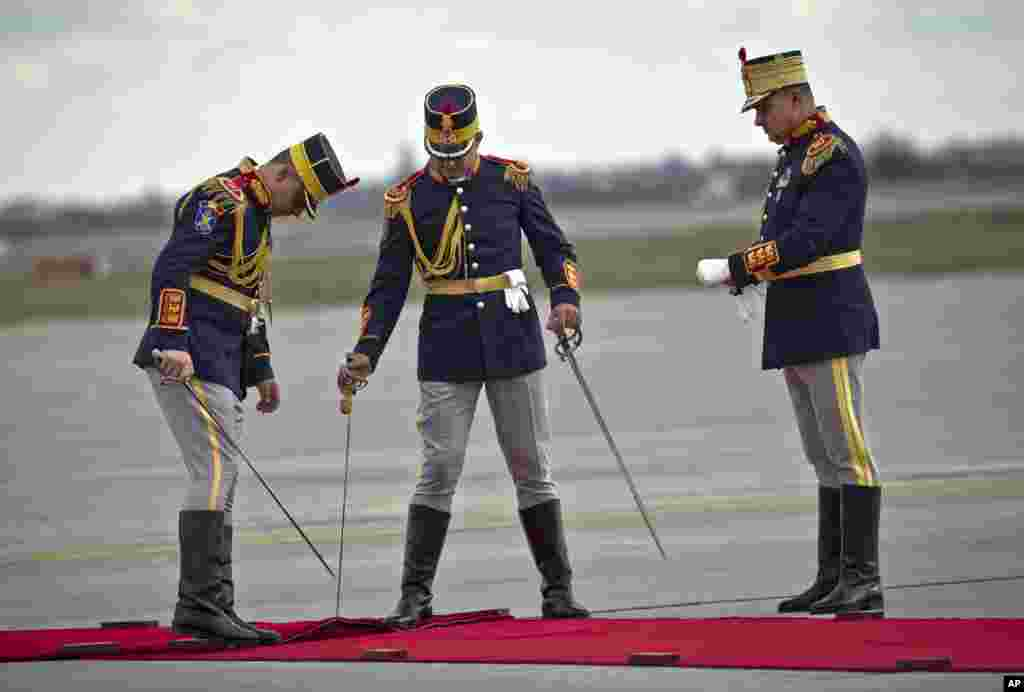 Honor guard soldiers position a red carpet before the arrival of China's Premier Li Keqiang at the Henri Coanda airport, outside Bucharest, Romania.