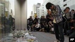 ທ້າວ Takashi Udagawa ນັກຮຽນມັດທະຍົມຍີ່ປຸ່ນອາຍຸ 15 ພວມອະທິຖານ ຫຼັງຈາກໄດ້ວາງຊໍ່ດອກໄມ້ສະ ແດງການຄາລະວະຕໍ່ ທ່ານ Steve Jobs ຜູ້ກໍ່ຕັ້ງບໍລິສັດ Apple ທີ່ເຖິງແກ່ມໍລະນະກຳ ໃນມື້ວັນພຸດວານນີ້ (6 ຕຸລາ 2011)