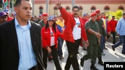 Venezuela's President Nicolas Maduro (C) gestures to supporters as he arrives for a ceremony commemorating the 22nd anniversary of late Venezuelan President Hugo Chavez's attempted coup d'etat in Caracas, Feb. 4, 2014.