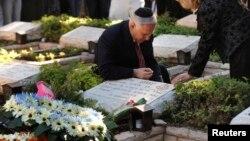 Le premier ministre israélien Benjamin Netanyahu allume une bougie pour commémorer la mort de son frère Yonathan sur sa tombe, mort en 1976 lors du raid israélien sur Entebbe, le 28 juin 2009.
