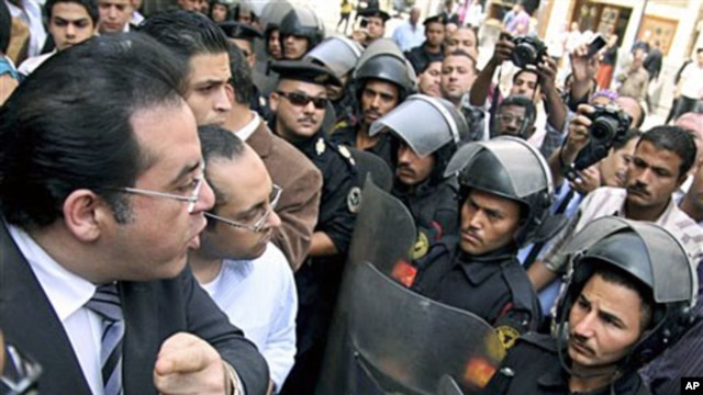 "Egyptian opposition politician Ayman Nour (L) argues with anti-riot policemen blocking the road in front of his party headquarters, as dozens of protesters chant ""freedom"" and call for amending the constitution to allow fairer presidential elections, Cair"