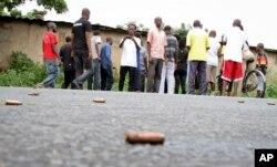 A man looks across at spent bullet casings lying on a street in the Nyakabiga neighborhood of Bujumbura, Burundi, Saturday, Dec. 12, 2015.