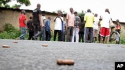 ຊາຍຄົນນຶ່ງ ກຳລັງຖ່າຍຮູບເອົາ ລູກປືນ ທີ່ຊະຊາຍໄປທົ່ວຖະໜົນ ໃນຄຸ້ມບ້ານ Nyakabiga ຂອງນະຄອນຫຼວງ Bujumbura, ປະເທດບູຣຸນດີ, ເມື່ອວັນເສົາ ທີ 12 ທັນວາ 2015.