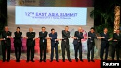 Leaders from the ASEAN and their Dialogue Partners which comprises the East Asia Summit or EAS, link hands for a brief group photo session at the ongoing 31st ASEAN Summit November 14, 2017 in Manila, Philippines.
