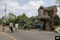 Residents walk past a fallen tree following a tornado that struck the night before in Pendleton, Ind., May 28, 2019.