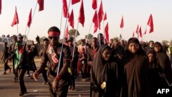Shi'ite Muslims march during the 40th anniversary of the Ashura religious ceremony in the village of Dakasoye, northern Nigeria, following a suicide bombing attack that killed at least 21 people near Kano, Nov, 27, 2015.