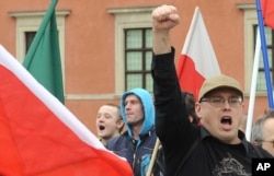 FILE - A supporter of a right wing organization gestures, as others shout slogans during an anti-migrant rally in Warsaw, Poland, Sept. 26, 2015.