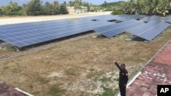 A Taiwanese Coast Guard member points to solar panels on disputed island Itu Aba in the South China Sea.
