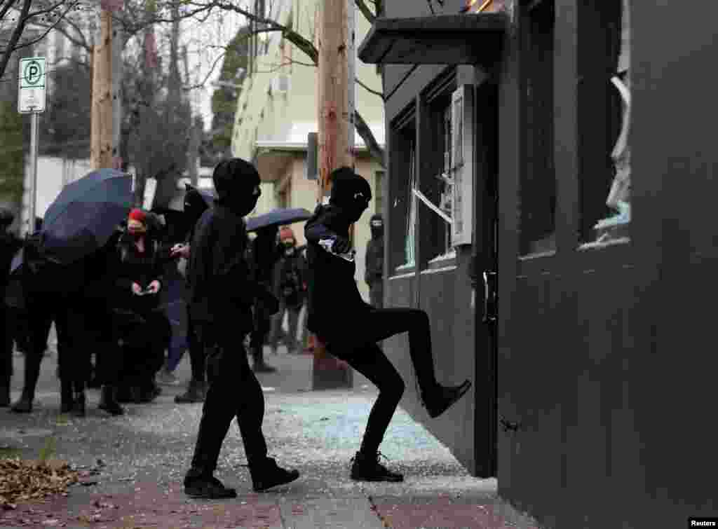 Protesters break windows at Democratic Party of Oregon headquarters during a protest after the swearing-in of U.S. President Joe Biden, in Portland, Oregon, Jan. 20, 2021.