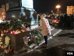 A woman approaches a memorial in Pushkin Square near the Kremlin, March 27, 2018, to those who died in a massive shopping mall blaze March 25 in the Siberian city of Kemerovo. A few hundred people were present at the vigil, though earlier there were a couple thousand at the site. (J. Dettmer/VOA)