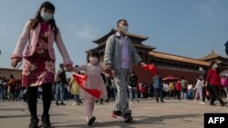 """十一""""长假期间游客们佩戴口罩游览故宫。"""
