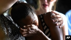 A woman cries during a church service to remember eight children who were killed in the Cairns suburb of Manoora, Australia, Dec. 21, 2014.