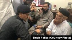 مفتی تقی عثمانی کی یہ تصویر سندھ پولیس نے جاری کی ہے جس میں وہ قاتلانہ حملے کے فوری بعد پولیس افسر سے بات کر رہے ہیں۔