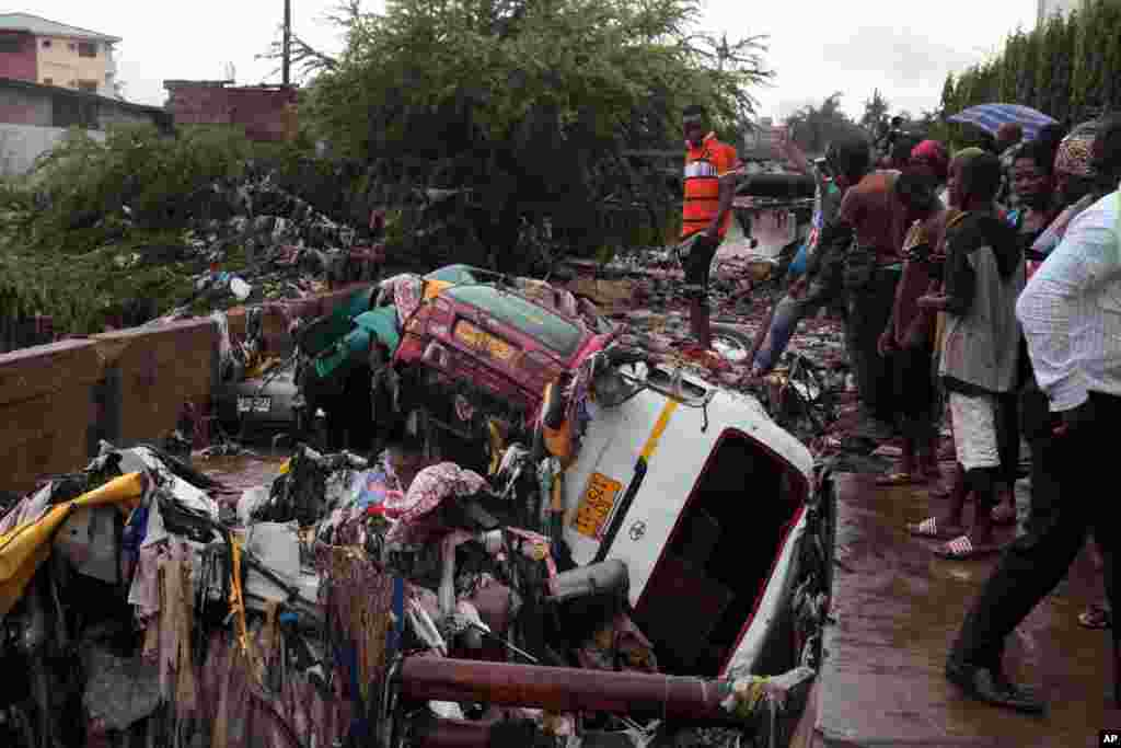 Cars are piled up after being washed away by heavy rain near a gas station in Accra, Ghana. Flooding in Ghana's capital swept stored fuel into a nearby fire, setting off a huge explosion at a gas station that killed at least 100, authorities said.