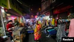 """一名非洲妇女走在中国广东省广州""""非洲村""""的夜市里,那里聚集着亚洲最多的非洲人口。(资料照片 2014年10月25日)"""