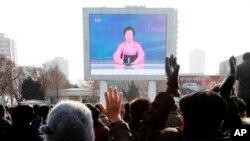 Warga Korea Utara menyaksikan penayangan siaran berita di luar stasiun kereta api Pyongyang di Pyongyang, Korea Utara (6/1).
