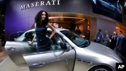 A hostess stands next to a Maserati Quattroporte during the first press day of the 65th Frankfurt Auto Show in Frankfurt, Germany, Sept. 10, 2013.