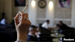 FILE - A woman holds a cigarette in a cafe in Vienna, Austria.