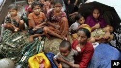 In this June 13, 2012 file photo, Rohingya Muslims who fled Burma to Bangladesh to escape religious violence, sit in a boat after being intercepted crossing the Naf River by Bangladeshi border authorities in Taknaf, Bangladesh.