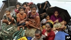 Rohingya Muslims who fled Myanmar to Bangladesh to escape religious violence, sit in a boat after being intercepted crossing the Naf River by Bangladeshi border authorities in Taknaf, Bangladesh, June 13, 2012.