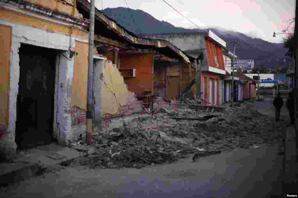 Two men walk past damaged houses after a 7.4-magnitude earthquake on the streets of San Marcos, Guatemala, November 8, 2012.