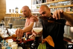 Shmuel Naky, right, pours beer during a press conference in Jerusalem, Wednesday, May 22, 2019. Israeli researchers raised a glass Wednesday to celebrate a long-brewing project of making beer and mead using yeasts extracted from ancient clay vessels.