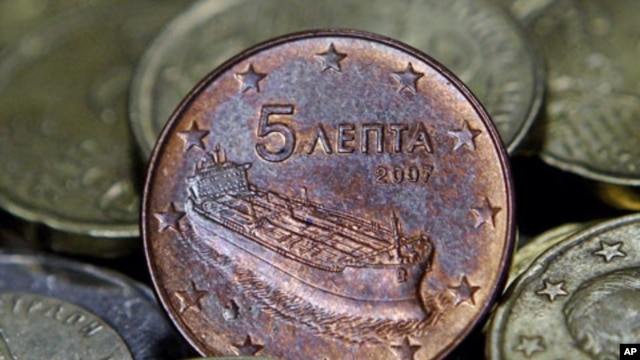 A Greek five-cent euro coin depicting a tanker is seen amongst other coins in Athens, Greece, February 15, 2012.