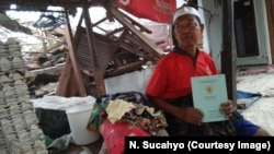Haji Fuadzi, resident of Pemenang County, North Lombok, holding up his land deed he found in the rubble of his concrete house.