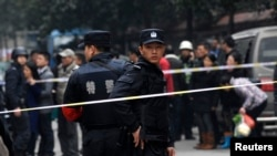 Police stand guard at a crime scene after a knifing incident in Changsha, Hunan province, March 14, 2014. At least three people are dead after the knifing incident in central China's Changsha city, state media reported on Friday, in what appeared to be a