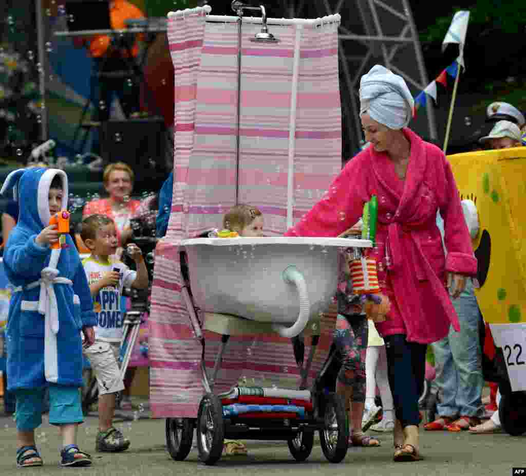 "A father (behind the shower curtain) pushes a self-made stroller designed to figure a bathtub during a ""stroller parade"" contest, as part of the celebrations for the International Children's Day in Stavropol, southeastern Russia."