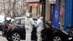 Des experts judiciaires examinent la voiture qui aurait été utilisée comme véhicule de secours par des hommes armés qui ont attaqué le bureau du journal satirique français Charlie Hebdo, à Paris, France, le 7 janvier 2015.